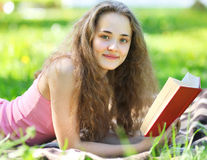 Portrait young happy girl reading a book lying in a park Royalty Free Stock Image