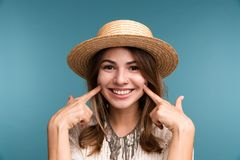 Portrait of a young happy girl in summer hat isolated over blue background stock photo
