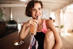 Portrait of young happy girl in swimsuit sitting in beach bar with sunglasses on counter and cocktail in hand. Beautiful royalty free stock images