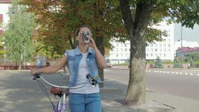 Portrait of a young, happy girl who walks around the city with a bicycle and drinks coffee stock video