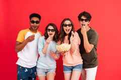 Portrait of a young happy group of multiracial friends. In 3d glasses having fun while standing together with popcorn isolated over red background royalty free stock image