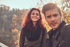 Portrait of young happy hikers walking at the beautiful autumn forest at sunset. royalty free stock images