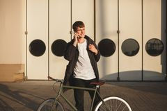 Young happy man with brown hair standing with classic bicycle and dreamily looking aside while talking on his cellphone. Portrait of young happy man with brown Royalty Free Stock Images
