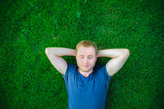 Portrait of a young happy man with closed eyes relaxing on the grass with his hands under the head. Selective focus. Stock Photos