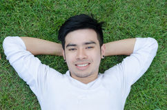 Portrait of a young happy man relaxing on the grass with his han Stock Images