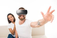 Portrait of young happy man sitting on sofa using virtual reality headset with girlfriend sitting behind, royalty free stock photography