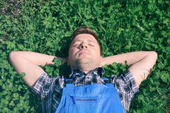 Portrait of a young happy man in working clothes relaxing on the grass with his hands under the head Stock Images