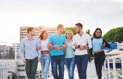 Portrait of a young and happy people at rest on the pier. Friends enjoying a game on the lake. Positive emotions. Stock Image