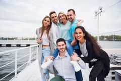 Portrait of a young and happy people at rest on the pier. Friends enjoying a game on the lake. Positive emotions. Royalty Free Stock Photos