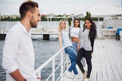 Portrait of a young and happy people at rest on the pier. Friends enjoying a game on the lake. Positive emotions. Royalty Free Stock Photo