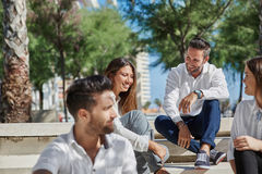 Young happy people sitting together outside laughing Royalty Free Stock Photo