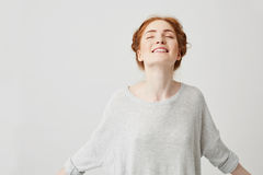 Portrait of young happy redhead girl smiling with closed eyes over white background. Royalty Free Stock Images