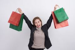 Portrait of young happy smiling Asian woman with shopping bags and holding shopping bags above her head Stock Images