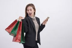 Portrait of young happy smiling Asian woman with shopping bags and smart phone royalty free stock photography
