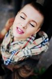 Portrait of young happy smiling girls with very short hair and c. Losed eyes wearing a scarf and coat. City lifestyle Stock Images