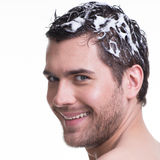 Portrait young happy smiling man washing hair. Stock Photos