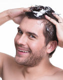 Portrait young happy smiling man washing hair. Royalty Free Stock Image