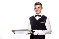 Portrait of young happy smiling waiter with on tray isolated on. A waiter or bartender, or servant holding a silver tray and smiling. White background Royalty Free Stock Photos