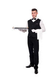 Portrait of young happy smiling waiter with on tray isolated on. A waiter or bartender, or servant holding a silver tray and smiling. White background Royalty Free Stock Photo