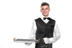 Portrait of young happy smiling waiter with on tray isolated on. A waiter or bartender, or servant holding a silver tray and smiling. White background Royalty Free Stock Image