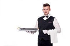 Portrait of young happy smiling waiter with on tray isolated on. A waiter or bartender, or servant holding a silver tray and smiling. White background Stock Photo