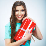 Portrait of young happy smiling woman hold red gift box. Isolat. Ed studio background female model Stock Photos