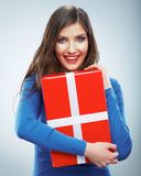 Portrait of young happy smiling woman hold red gift box. Isolat. Ed studio background female model Royalty Free Stock Photo