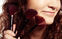 Portrait of smiling woman with make up tools Stock Images