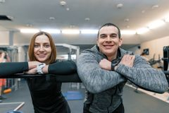Portrait of young happy sporty couple, man and woman smiling looking into the camera, gym background stock photo