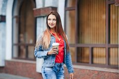 Portrait of young happy stylish woman in blue jeans and red shirt walking in the city centre and drinking coffee. Royalty Free Stock Images