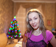 Portrait of the young happy woman against a New Year's tree Stock Photo