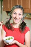 Portrait of young happy woman eating salad at home Royalty Free Stock Photos