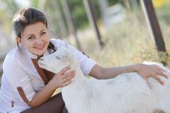 Portrait of young happy woman with goat Royalty Free Stock Photo