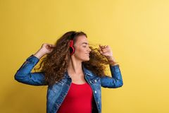 Portrait of a young woman with headphones in a studio on a yellow background. Portrait of a young happy woman with headphones in a studio on a yellow background stock image