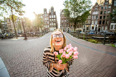 Woman with tulips in Amsterdam city. Portrait of a young and happy woman holding a bouquet of pink tulips standing outdoors in Amstredam city Royalty Free Stock Image