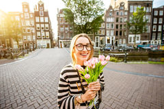 Woman with tulips in Amsterdam city. Portrait of a young and happy woman holding a bouquet of pink tulips standing outdoors in Amstredam city Royalty Free Stock Photography
