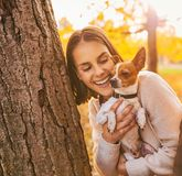 Portrait of young happy woman holding little cute dog Royalty Free Stock Image