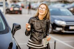 Woman renting a car. Portrait of a young happy woman with keys and rental contract standing near the car on the outdoor parking Stock Photography
