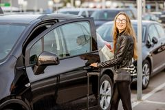 Woman renting a car. Portrait of a young and happy woman opening the door of the rental car outdoors on the parking Royalty Free Stock Photos