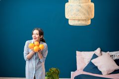 Woman with oranges on the blue background Royalty Free Stock Photography