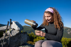 Portrait of young happy woman pouring tea out of thermos Royalty Free Stock Images