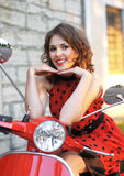 Portrait of a young and happy woman on a scooter Stock Photos