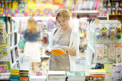 Portrait of young happy woman shopping in bookstore. Portrait of happy beautiful caucasian person standing in bookstore and looking through books with a smile royalty free stock photos
