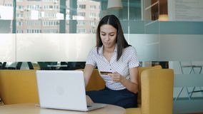 Young woman using credit card online. Portrait of a young happy  woman sitting in front of a monitor - making a purchase using a credit card online. People stock stock video