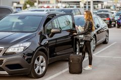 Woman renting a car. Portrait of a young and happy woman traveling with suitcase near the rental car outdoors on the parking Royalty Free Stock Photography