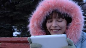 A young woman in a warm jacket uses a digital tablet in the park in the winter. Portrait of a young happy woman uses a digital tablet and sitting on a bench in stock video