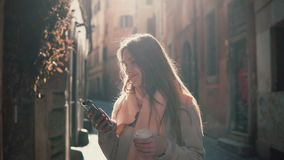 Portrait of young happy woman walking in city and using smartphone. Girl browse the Internet and drinking coffee. Royalty Free Stock Photography