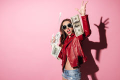 Portrait of a young happy woman winner throwing money banknotes. Isolated over pink Royalty Free Stock Photo