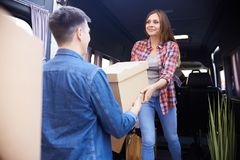Couple Loading Moving Van. Portrait of young happy women unloading boxes from moving van handing them to smiling husband Stock Image