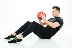 Portrait of a young healthy athlete man doing abdominal exercises Stock Photo